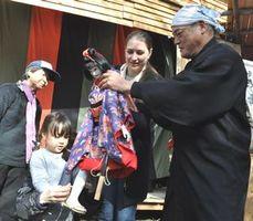 あわ工芸座の座員(右端)から人形の遣い方を学ぶ外国人親子ら=徳島中央公園