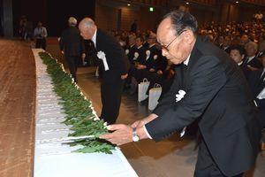 戦没者をしのび献花する参列者=徳島市のあわぎんホール