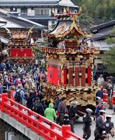 岐阜県高山市で「春の高山祭」が始まり、市中心部の橋を渡る豪華な屋台=14日午前
