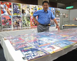 高校野球を特集した雑誌に見入る来場者=徳島市の市立木工会館