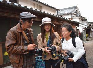 受講生の写真に助言する勇崎さん(左)=美馬市脇町のうだつの町並み