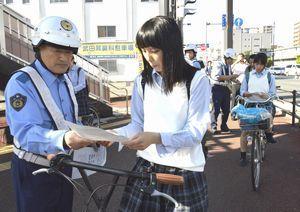 自転車の高校生らにチラシを配り講習制度を説明する東署員=徳島市の徳島本町交差点