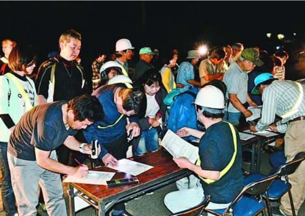 夜間の防災訓練で避難所に集まる住民=阿波市阿波町の林小