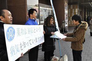 薬物依存症への理解を訴え、チラシを配る徳島ダルクの入所者ら=徳島駅前