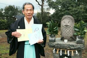 園児が妖怪「アマビエ」に宛てて書いた手紙を手にする大島子諏訪神社の山浦一男宮司=12日、熊本県天草市(同市提供)