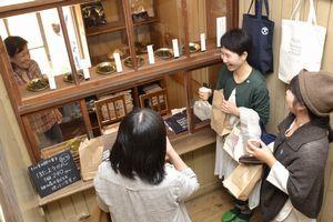 購買で茶の飲み比べを楽しむ来場者=神山町下分の旧左右内小