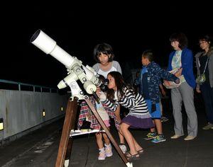 望遠鏡を使って月を鑑賞する参加者=阿南市那賀川町の市科学センター