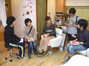 ポスター制作のため、店主(中央)に取材する四国大の学生=北島町高房