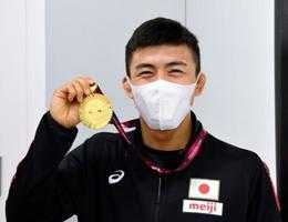 優勝したアジア選手権から帰国し、笑顔でメダルを掲げるレスリングの文田健一郎=21日、成田空港