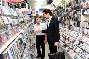 8月の閉店が決まり、客と音楽談義を交わす「ディスクステーションAWA」の木村店長(左)=徳島市寺島本町東
