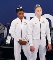 女子団体総合決勝でチームメートの演技を見守る米国のシモーン・バイルス(左)=27日、有明体操競技場