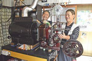 映写機を前に笑顔を見せる山口さん(右)と大下さん=三好市西祖谷山村