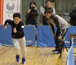 桧山さんらに見守られ、10メートル走のタイムを測る参加者=徳島市立体育館