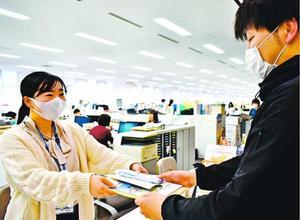 妊婦のいる世帯にマスクを配布する職員(左)=阿波市役所