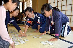 真剣な表情で札を取り合う参加者=徳島市の徳島城博物館