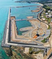 米軍普天間飛行場の移設先として、埋め立てが進む沖縄県名護市辺野古の沿岸部。14日で土砂投入を始めて1年となる=13日午後(小型無人機から)