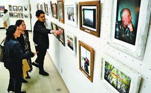来場者に写真について説明する隼平さん(右端)=徳島市のあわぎんホール
