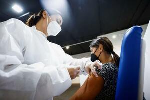 モデルナ製ワクチンの接種を受ける女性=5日、ローマ(ロイター=共同)