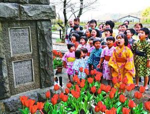慰霊碑にチューリップを飾って「第九」を歌う「エベレスト・ザ」のメンバー=鳴門市の板東俘虜収容所跡
