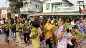 13日、ミャンマー・ダウェーでティンジャン(ミャンマー正月)を祝う植木鉢を持ち国軍に抗議する市民ら(Dawei Watch提供、ロイター=共同)