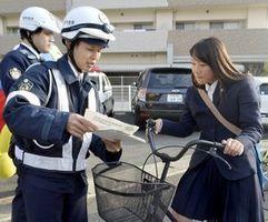 チラシを配って条例の施行を周知する徳島西署員=徳島市の田宮交番前