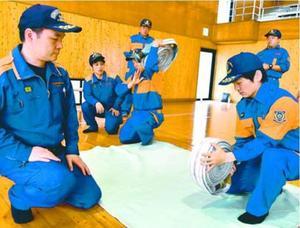 小松島市消防本部の職員(左の2人)からホースの扱い方を教わる団員=同市立江町赤石の市立武道館