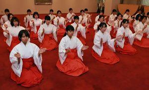真剣な表情で「二礼二拍手一礼」の参拝方法を学ぶ女性=鳴門市大麻町の大麻比古神社