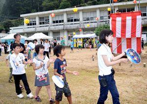 校舎をバックに「木頭踊り」を披露する児童=北川小グラウンド