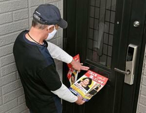 アパート周辺の住宅に情報提供を呼び掛けるビラを投函する五條堀美咲さんの父親=26日午後、大分市