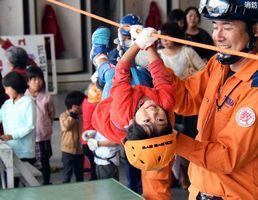 「スリング」でロープにぶら下がり、懸命に進もうとする子ども=北島町の県立防災センター