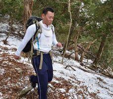 雪の積もった山道を重りを背負って走る参加者=那賀町沢谷