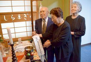 白菊特攻隊員の冥福を祈って千羽鶴を納める大塚さん夫妻と新保さん(右)=松茂町の海上自衛隊徳島航空基地