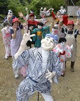 盆踊りを踊るかかしと阿川28歩の会のメンバー=神山町阿野