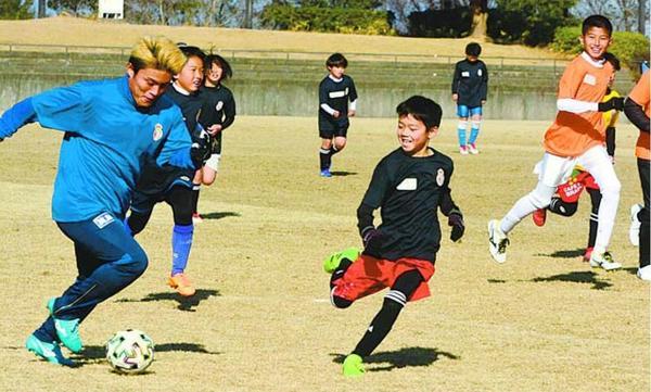 表原選手(左端)らとサッカーを楽しむ子どもたち=徳島市球技場