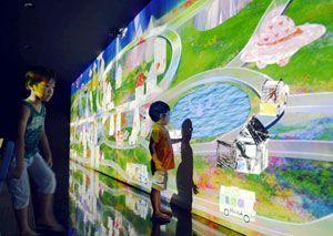 デジタル画像の街の中に現れたバスや家を触って楽しむ子ども=徳島市の東新町1丁目商店街の特設会場