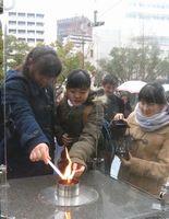 「希望の灯り」を分灯する津田中学校の生徒=神戸市