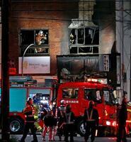 火災があった居酒屋を調べる消防隊員=11日午後8時50分、名古屋市千種区