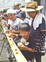 流しそうめんを楽しむお年寄りと子どもたち=三好市池田町の馬路放課後児童クラブ