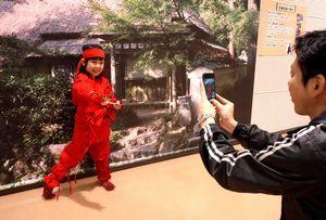 忍者の衣装を身に着け、記念撮影をする親子=板野町のあすたむらんど徳島