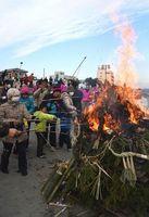無病息災を願い、やぐらの火でミカンを焼く参加者=鳴門市撫養町の岡崎海岸