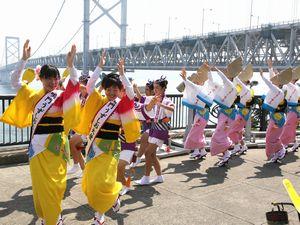 大鳴門橋をバックに初踊りを披露する「なると市連」の踊り子ら=午前10時ごろ、鳴門市鳴門町の鳴門公園千畳敷
