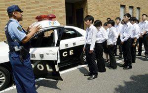 インターンシップで警察官からパトカーの車内設備の説明を聞く学生たち=県警本部