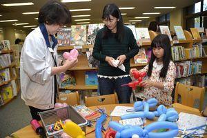 バルーンアートに挑戦する親子連れ=板野町の県立総合教育センター