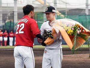 引退試合で広島の中村奨(左)から花束を受け取るオリックスの西浦颯大外野手=オセアンバファローズスタジアム舞洲