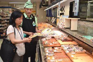 生鮮食品の表示を確かめる県の食品表示Gメンの職員(手前)=そごう徳島店