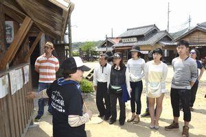 「バルトの庭」で市民ガイド(写真手前)の解説に耳を傾ける観光客=鳴門市大麻町桧