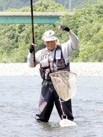 アユを仕留め、顔をほころばせる釣り人=阿南市加茂町の那賀川