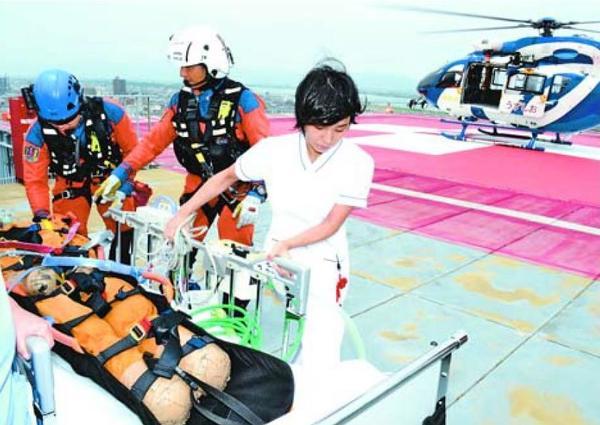 防災ヘリで搬送された負傷者の受け入れ訓練に取り組む看護師(右)=徳島市民病院