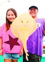 金色のエイを見つけて捕獲した土肥さん(左)と武知さん=阿南市の中林漁港