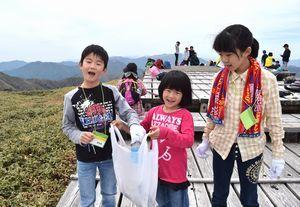 山頂近くの遊歩道沿いに落ちているごみを拾う子どもら=剣山